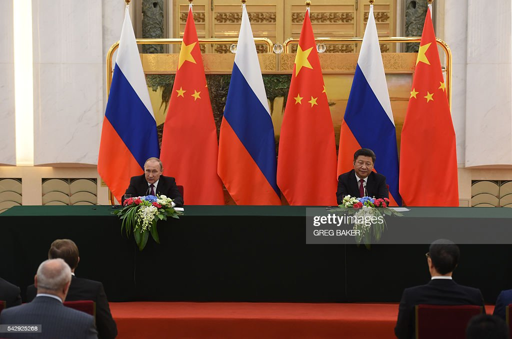 Russian President Vladimir Putin (L) speaks as Chinese President Xi Jinping looks on during a joint press briefing in Beijing's Great Hall of the People on June 25, 2016. / AFP / POOL / GREG