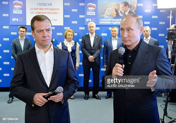 Russian President Vladimir Putin speaks as Prime Minister and chairman of the United Russia political party Dmitry Medvedev listens at the party's...