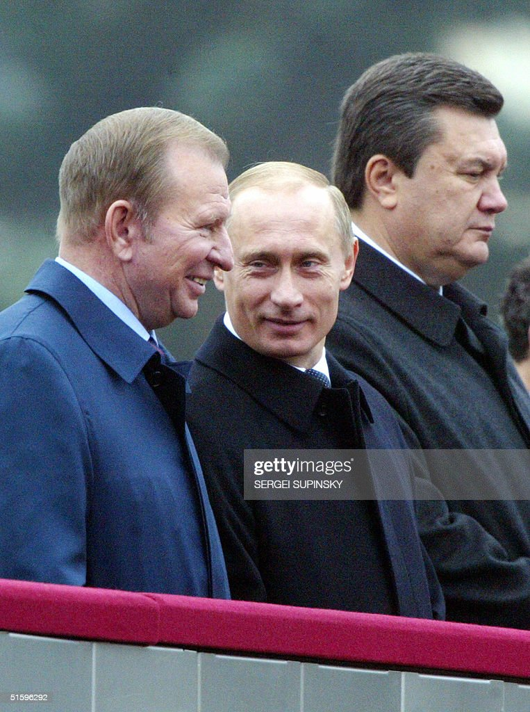 Russian President <a gi-track='captionPersonalityLinkClicked' href=/galleries/search?phrase=Vladimir+Putin&family=editorial&specificpeople=154896 ng-click='$event.stopPropagation()'>Vladimir Putin</a> (C) speaks to his Ukrainian counterpart <a gi-track='captionPersonalityLinkClicked' href=/galleries/search?phrase=Leonid+Kuchma&family=editorial&specificpeople=239079 ng-click='$event.stopPropagation()'>Leonid Kuchma</a> (L) as Ukrainian Prime Minister and presidential candidate Viktor Yanukovich (R) stands next to them during a millitary parade in Kiev 28 October 2004. Putin, along with other leaders of former Soviet states, arrived in Kiev to attend festivities marking the 60th anniversary of the liberation of Ukraine from the Nazi occupation during World War II, three days before Ukraine's presidential elections 31 October. AFP PHOTO/ Sergei SUPINSKY