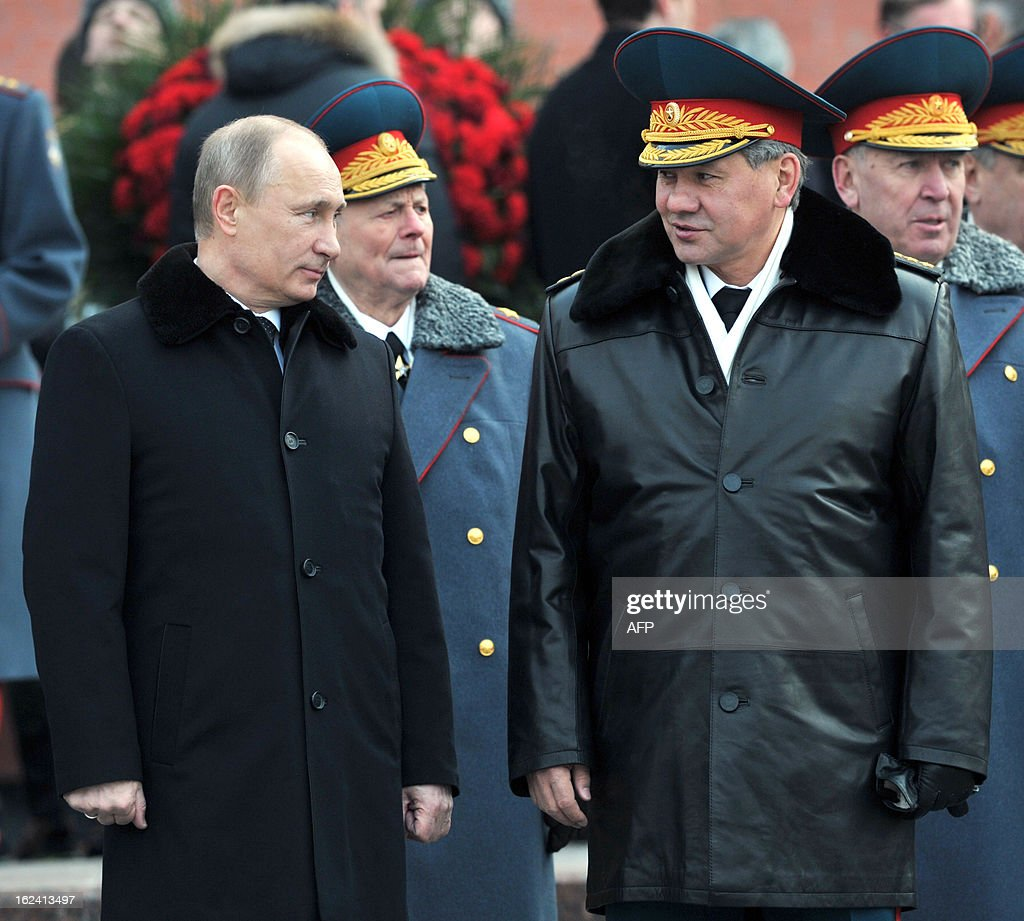 Russian President Vladimir Putin (L) speaks with Defence Minister Sergei Shoigu (R) as they attend the ceremony of laying flowers to the Tomb of the Unknown Soldier by the Kremlin wall to mark the Defenders of the Fatherland Day holiday in Moscow on February 23, 2013. The Defenders of the Fatherland Day, celebrated in Russia on February 23, honors the nation's army and is a nationwide holiday. AFP PHOTO / RIA NOVOSTI / PRESIDENTIAL PRESS SERVICE / ALEXEY NIKOLSKY