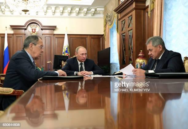 Russian President Vladimir Putin speaks with Defence Minister Sergei Shoigu and Foreign Minister Sergei Lavrov during their meeting at the Kremlin in...
