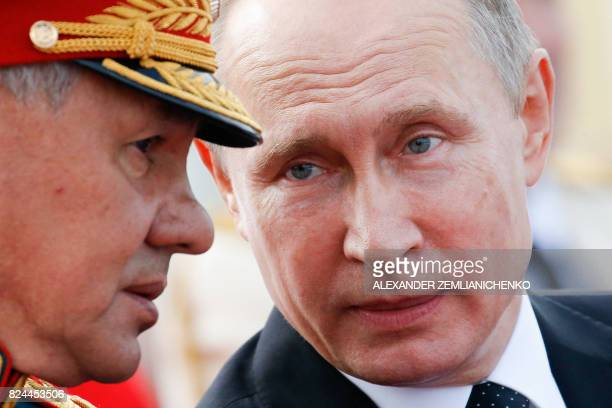 Russian President Vladimir Putin speaks with Defence Minister Sergei Shoigu as they attend a ceremony for Russia's Navy Day in Saint Petersburg on...