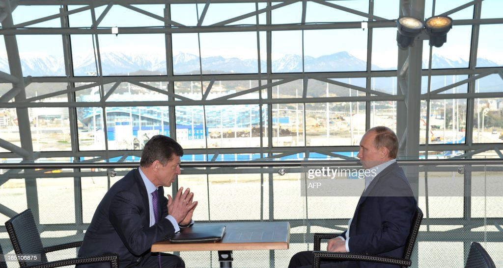 Russian President Vladimir Putin (R) speaks with Deputy Prime Minister Dmitry Kozak during a meeting with representatives of ice hockey and figure skating federations of Russia at the Bolshoy ice dome in Sochi on March 30, 2013.
