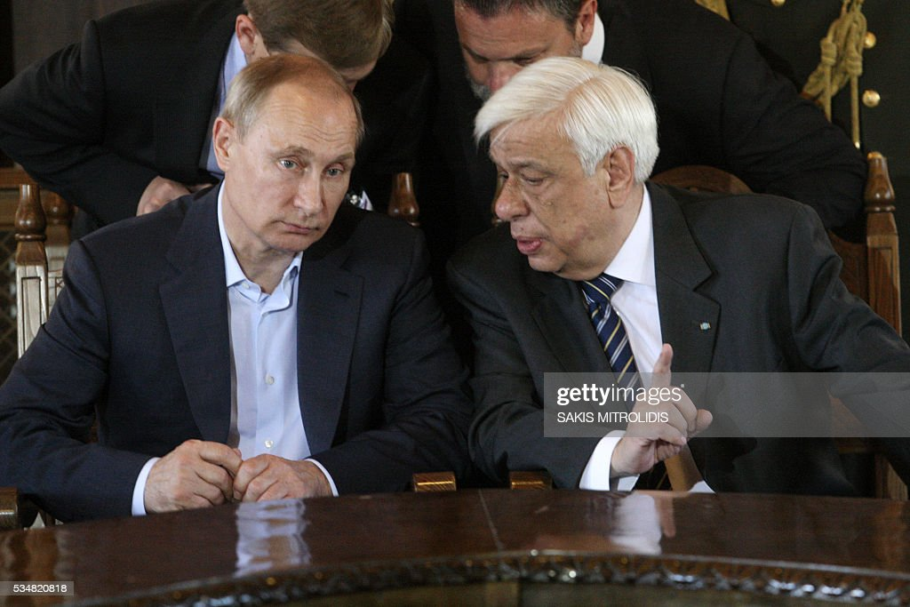 Russian President Vladimir Putin (L) speaks with Greek President Prokopis Pavlopoulos (R) during a visit to the monastic community of Mount Athos, in Karyes on May 28, 2016. Putin, who has often talked about his strong Orthodox faith, will join celebrations for the 1,000th anniversary of the Russian presence at the ancient, all-male monastic community of Mount Athos. The visit, Putin's first to the EU since December, comes at a low ebb in relations between Russia and Europe over the conflict in Ukraine that broke out in 2014, with sanctions still in force against Moscow. / AFP / SAKIS