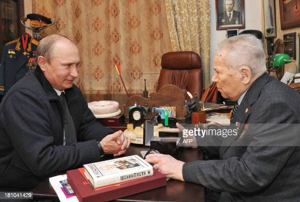 Russian President Vladimir Putin speaks with Mikhail Kalashnikov the Russian inventor of the globally popular AK47 assault rifle during his working...