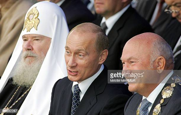 Russian President Vladimir Putin speaks with Moscow's Mayor Yuri Luzhkov as Russian Orthodox Patriarch Alexi II sits next to them during the Day of...