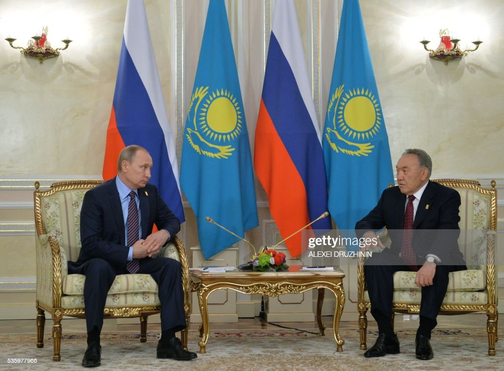 Russian President Vladimir Putin (L)speaks with President of Kazakhstan Nursultan Nazarbayev during their meeting in Astana on May 31, 2016. / AFP / POOL / ALEXEI