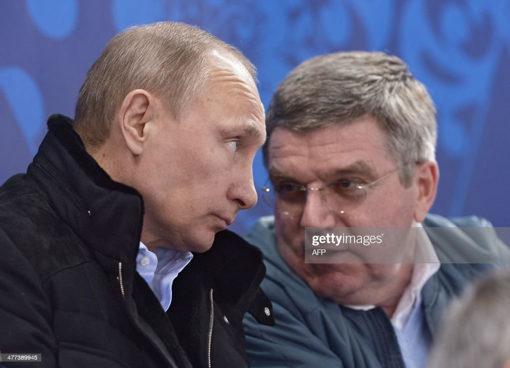 Russian President Vladimir Putin (L) speaks with President of the International Olympic Committee Thomas Bach (R) during a qualifying round match between the teams of Russia and the Republic of Korea in the ice sledge hockey tournament at the Sochi 2014 Winter Paralympics on March 8, 2014.