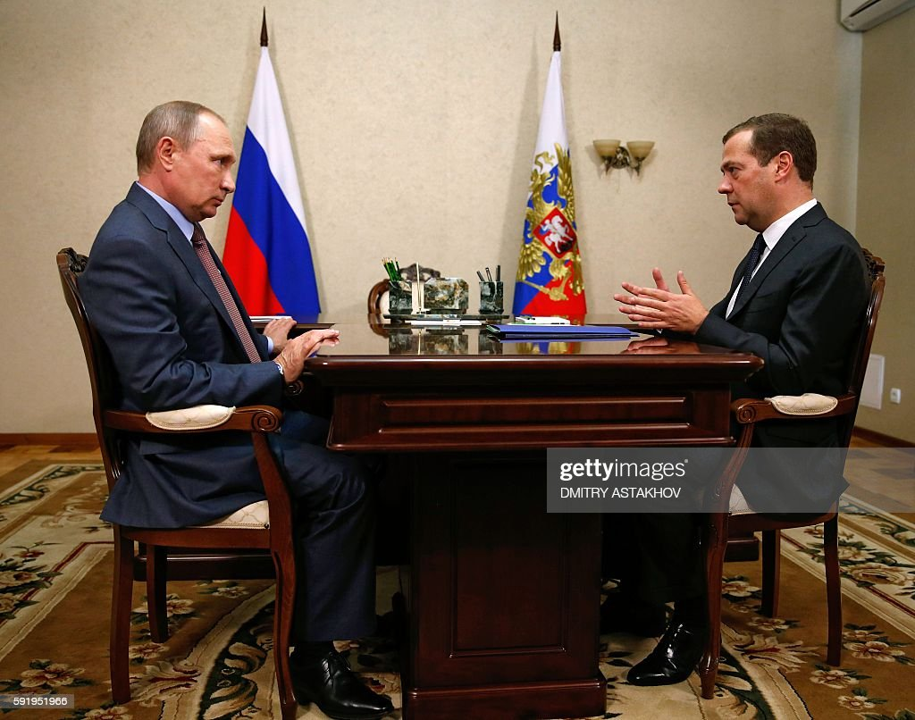 TOPSHOT Russian President Vladimir Putin speaks with Prime Minister Dmitry Medvedev during their meeting at the Belbek airport near the Black sea...