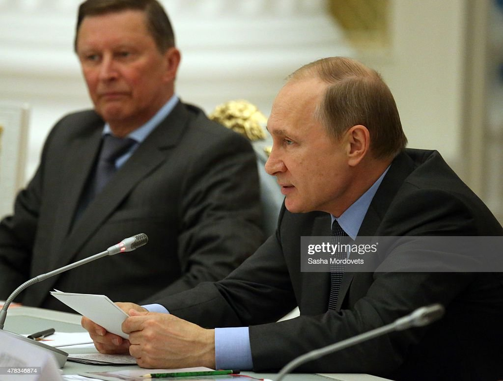 Russian President Vladimir Putin speeches as Presidential Administration Chief of Staff Sergei Ivanov looks on during a meeting with Presidential...