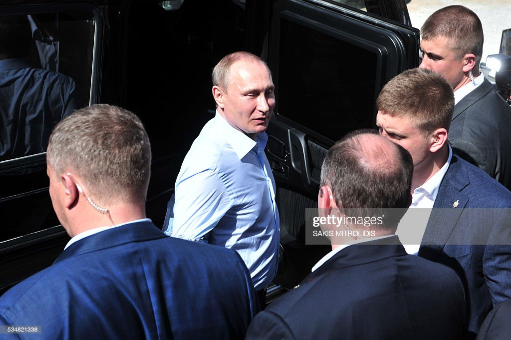 Russian President Vladimir Putin (C) stands in front of a car during a visit to the monastic community of Mount Athos, in Karyes on May 28, 2016. Putin, who has often talked about his strong Orthodox faith, will join celebrations for the 1,000th anniversary of the Russian presence at the ancient, all-male monastic community of Mount Athos. The visit, Putin's first to the EU since December, comes at a low ebb in relations between Russia and Europe over the conflict in Ukraine that broke out in 2014, with sanctions still in force against Moscow. / AFP / SAKIS