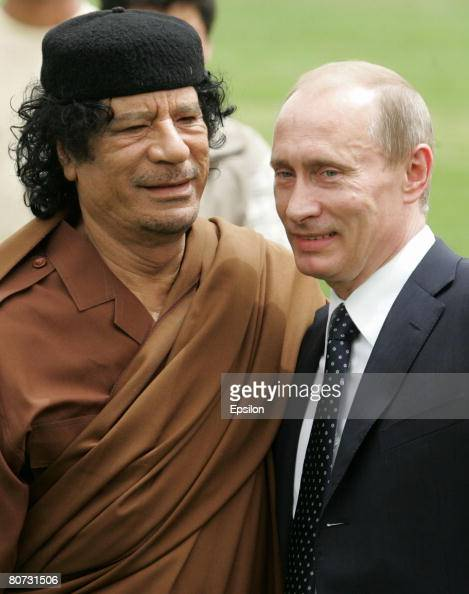 Russian President Vladimir Putin stands next to Libyan leader Muammar Qadaffi during the signing of agreements between the two countries April 17...