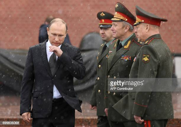 Russian President Vladimir Putin stands under pouring rain during a ceremony marking the 76th anniversary of the Nazi German invasion by the Kremlin...