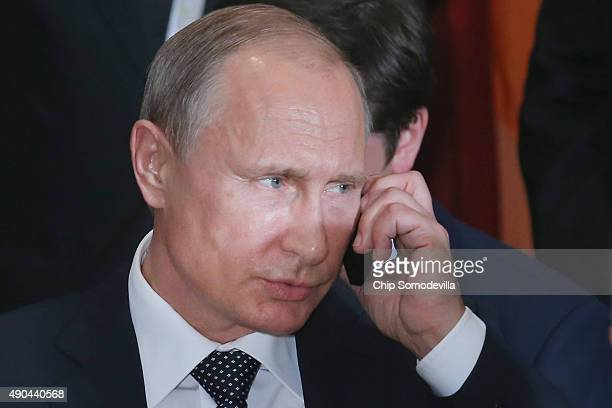 Russian President Vladimir Putin takes a call during a luncheon hosted by United Nations SecretaryGeneral Ban Kimoon at the 70th annual UN General...