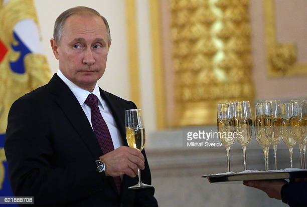 Russian President Vladimir Putin takes a glass of champagne during the reception for new foreign ambassadors at Grand Kremlin Palace on November 9...