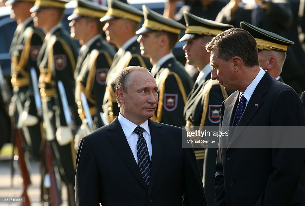 Russian President Vladimir Putin talks to Slovenian President Borut Pahor while visiting a newly opened monunent to WWII vicitims in Ljubljana...