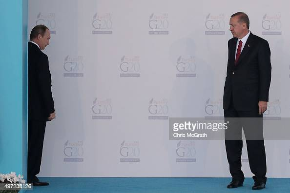 Russian President Vladimir Putin talks with Turkish President Recep Tayyip Erdogan before leaving the arrival area during the official welcome...