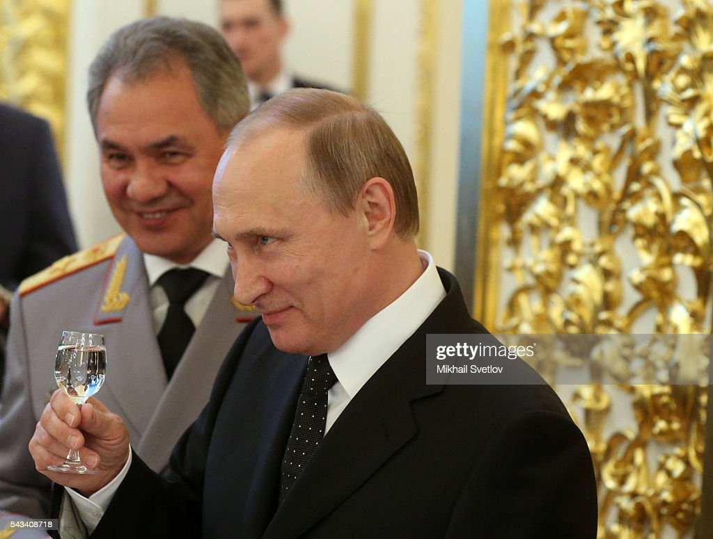 Russian President Vladimir Putin (C) toasts holding a glass of vodka as Defence Minister Sergei Shoigu (L) looks on during the reception for graduates of military academies and universtities at the Grand Kremlin Palace on June 28, 2016 in Moscow, Russia.