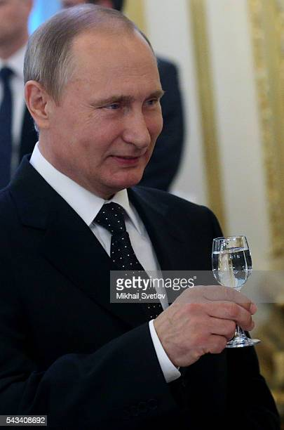 Russian President Vladimir Putin toasts holding a glass of vodka during the reception for graduates of military academies and universtities at the...