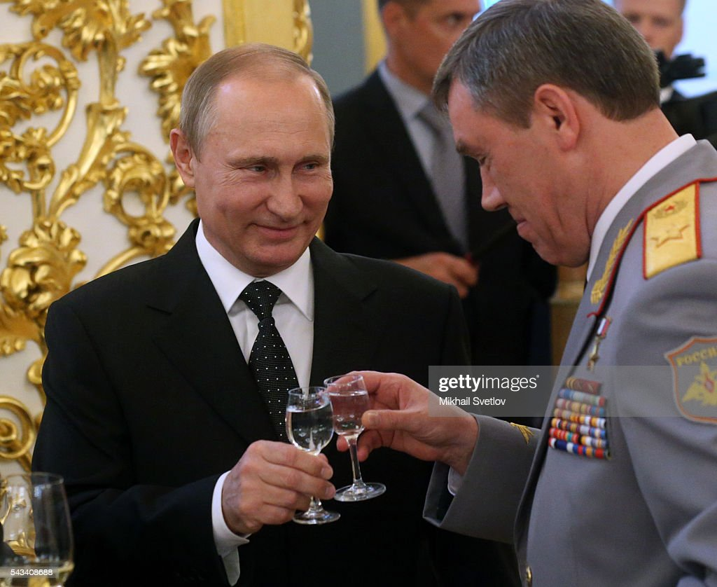 Russian President Vladimir Putin (C) toasts holding a glass of vodka with Deputy Defence Minister Valery Gerasimov (L) during the reception for graduates of military academies and universtities at the Grand Kremlin Palace on June 28, 2016 in Moscow, Russia.