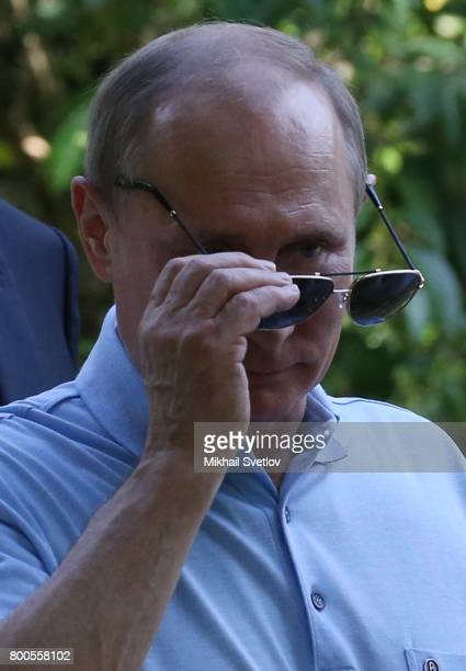 Russian President Vladimir Putin touches his sunglasses while visiting Artek camp an international children center on the Black Sea on June 24 2017...