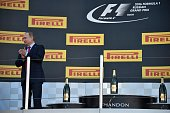 Russian President Vladimir Putin waits on the podium to award the winner after the Formula One Russian Grand Prix at the Sochi Autodrom circuit on...