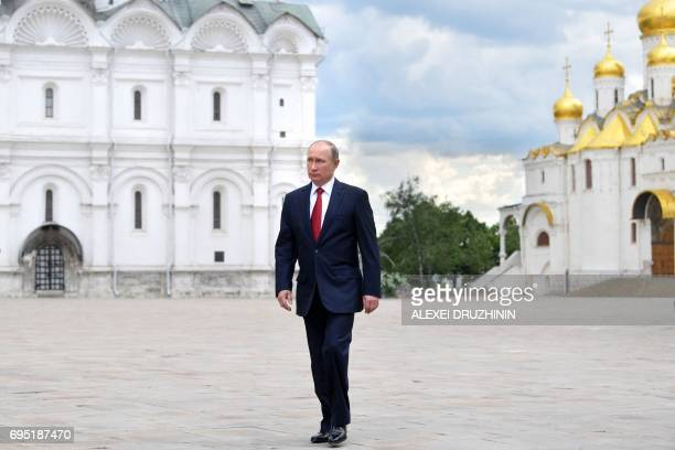 Russian President Vladimir Putin walks along the Cathedral Square of the Kremlin before a holiday reception marking 'Russia Day' in Moscow on June 12...