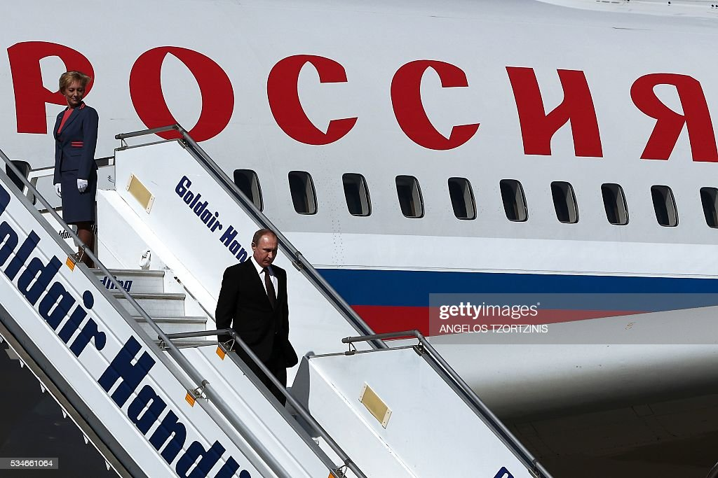 Russian President Vladimir Putin (C) walks down from his plane at the Athens international Airport, at the start of his trip to Greece aiming to reinforce a relationship with one of his few friends in the EU amid continuing diplomatic tensions with the West on May 27, 2016. / AFP / ANGELOS