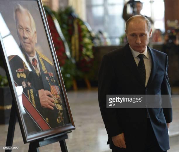 Russian President Vladimir Putin walks past a portrait of Mikhail Kalashnikov the designer of the iconic AK47 assault rifle that was the favoured...