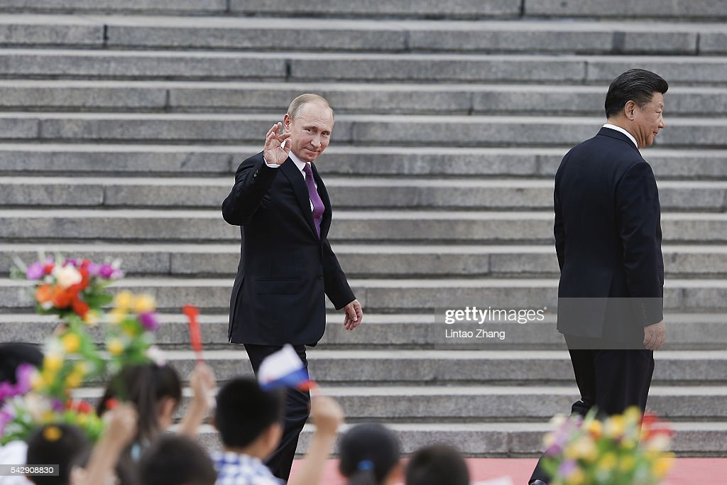 Russian President <a gi-track='captionPersonalityLinkClicked' href=/galleries/search?phrase=Vladimir+Putin&family=editorial&specificpeople=154896 ng-click='$event.stopPropagation()'>Vladimir Putin</a> (L) wave to Chinese children with Chinese President <a gi-track='captionPersonalityLinkClicked' href=/galleries/search?phrase=Xi+Jinping&family=editorial&specificpeople=2598986 ng-click='$event.stopPropagation()'>Xi Jinping</a> after a welcoming ceremony outside the Great Hall of the People on June 25, 2016 in Beijing, China. At the invitation of President <a gi-track='captionPersonalityLinkClicked' href=/galleries/search?phrase=Xi+Jinping&family=editorial&specificpeople=2598986 ng-click='$event.stopPropagation()'>Xi Jinping</a>, Russian President <a gi-track='captionPersonalityLinkClicked' href=/galleries/search?phrase=Vladimir+Putin&family=editorial&specificpeople=154896 ng-click='$event.stopPropagation()'>Vladimir Putin</a> is in China to discuss more economic and military cooperation between the two countries.