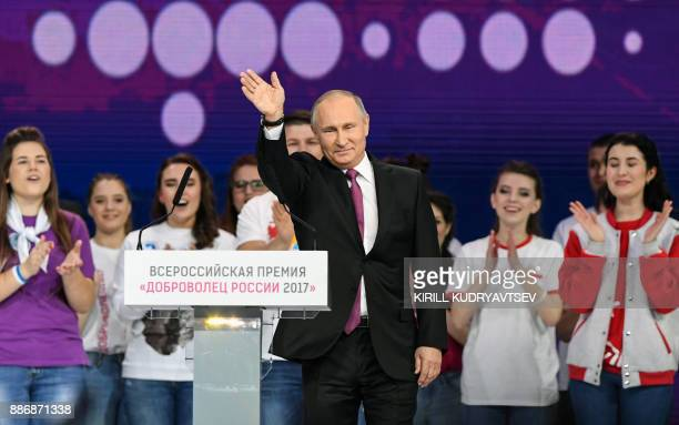 Russian President Vladimir Putin waves after delivering a speech at a forum of volunteers in Moscow on December 6 2017 / AFP PHOTO / Kirill...