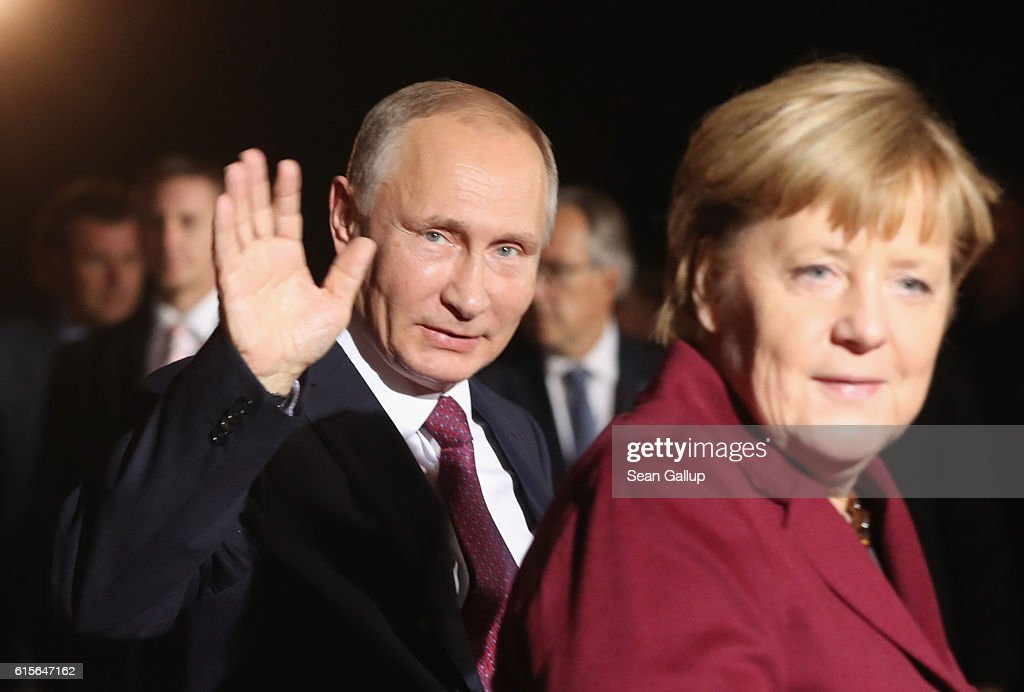 Russian President Vladimir Putin waves as he walks with German Chancellor Angela Merkel upon his arrival to discuss the Ukrainian peace process at the Chancellery on October 19, 2016 in Berlin, Germany. The leaders of Russia, Ukraine, France and Germany, known as the Normandy Four, are meeting to discuss implementation of the peace plan known as the Minsk Protocol, a roadmap for resolving the conflict in Ukraine after Russian forces invaded in 2014 and annexed the peninsula of Crimea. The United States has threatened renewed sanctions on Russia if the country did not either implement the plan in the coming months or arrive at a plan on how to do so.
