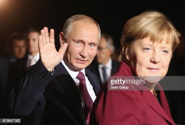 Russian President Vladimir Putin waves as he walks with German Chancellor Angela Merkel upon his arrival to discuss the Ukrainian peace process at...