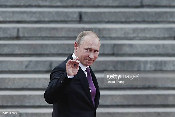Russian President Vladimir Putin waves to Chinese children after a welcoming ceremony outside the Great Hall of the People on June 25 2016 in Beijing...