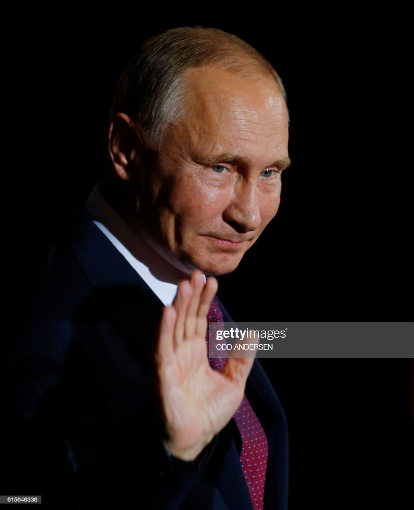 Russian President Vladimir Putin waves upon arrival at the chancellery on October 19, 2016 in Berlin. German Chancellor Angela Merkel hosts the leaders of Russia, Ukraine and France in a new push for peace in eastern Ukraine. / AFP / Odd ANDERSEN