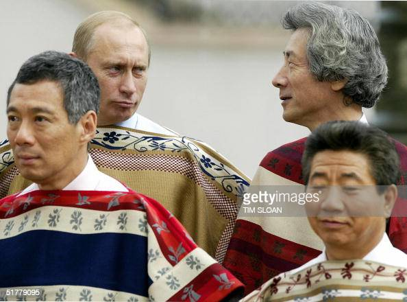 Russian President Vladimir Putin wearing a traditional Chilean poncho poses with Singapore's Prime Minister Lee Hsien Loong Japan's Prime Minister...