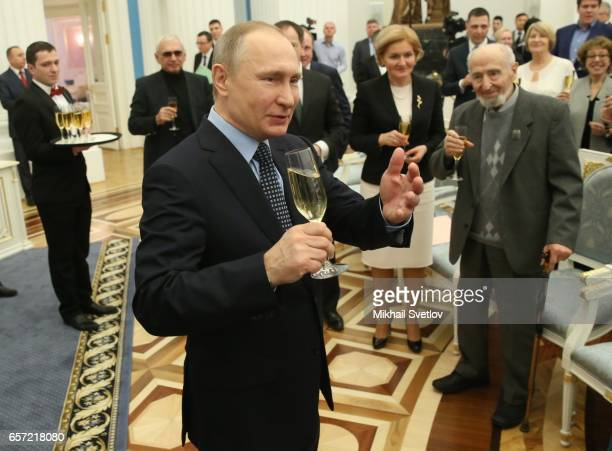 Russian President Vladimir Putin with a glass of champagne during the awards ceremony at the Kremlim on March 2017 in Moscow Russia has awarded 6...