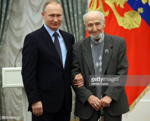Russian President Vladimir Putin with animator and film director Leonid Shwartsman speaks during the awards ceremony at the Kremlim on March 2017 in...