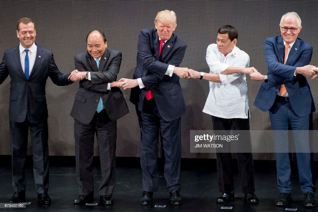 TOPSHOT - (L-R) Russian Prime Minister Dmitry Medvedev, Vietnam's Prime Minister Nguyen Xuan Phuc, US President Donald Trump, Philippine President Rodrigo Duterte and Australia Prime Minister Malcolm Turnbull join hands for a family photo during the opening ceremony of the 31st Association of South East Asian Nations (ASEAN) Summit in Manila on November 13, 2017. World leaders are in the Philippines' capital for two days of summits. /