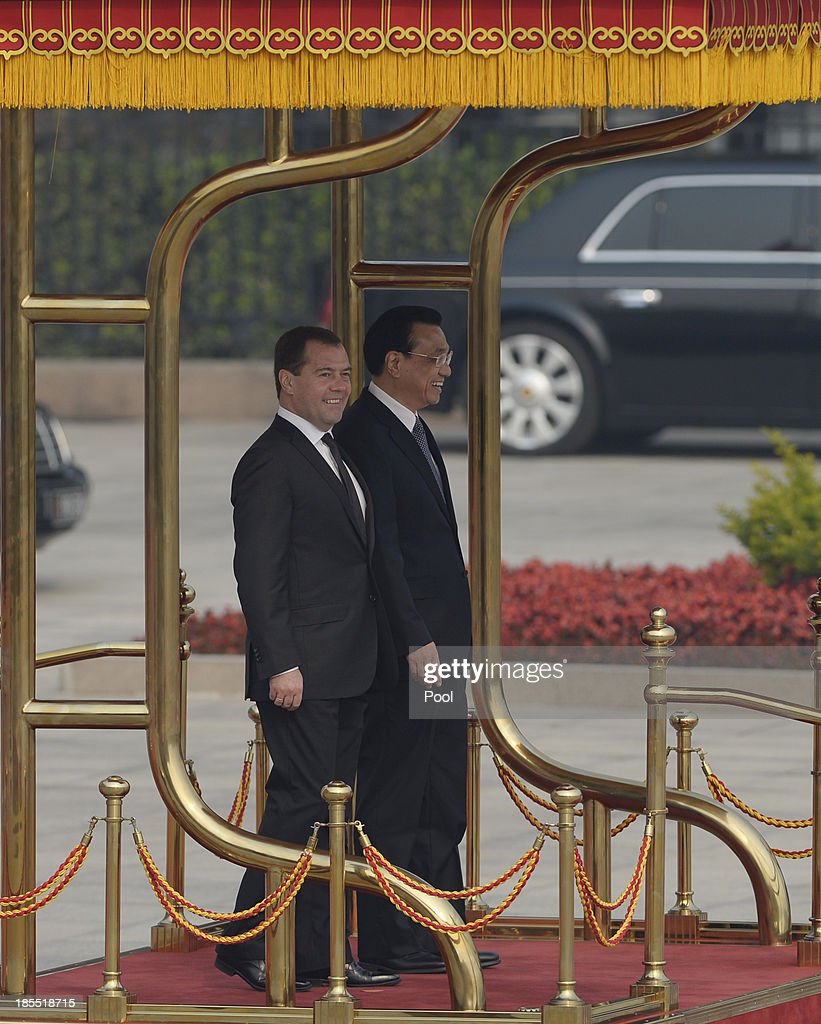 Russian Prime Minister Dmitry Medvedev and Chinese Premier Li Keqiang attend a welcoming ceremony outside at the Great Hall of the People on October 22, 2013 in Beijing, China. Medvedev is in China on a two-day visit as a guest of Chinese Premier Li Keqiang to co-chair the 18th regular meeting between the Chinese and Russian heads of government.