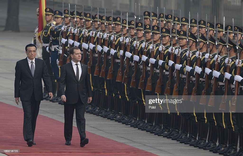 Russian Prime Minister Dmitry Medvedev (R) and Chinese Premier Li Keqiang (L) inspect an honour guard at a welcoming ceremony outside at the Great Hall of the People on October 22, 2013 in Beijing, China. Medvedev is in China on a two-day visit as a guest of Chinese Premier Li Keqiang to co-chair the 18th regular meeting between the Chinese and Russian heads of government.