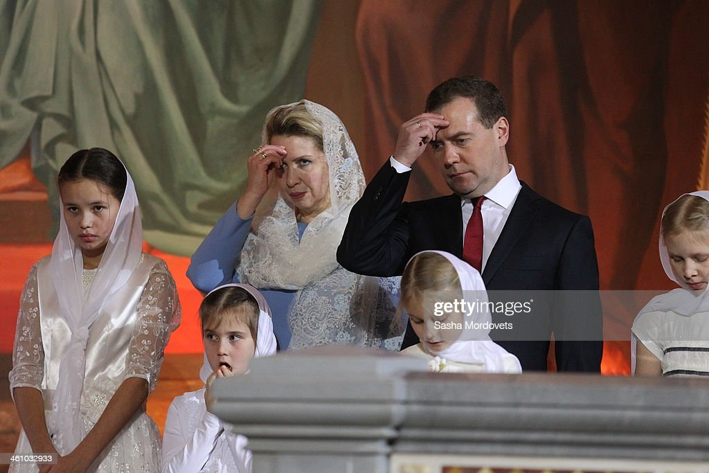 Russian Prime Minister Dmitry Medvedev (2R) and his wife Svetlana Medvedeva (3R) pray during the Christmas Mass in the Christ the Saviour Cathedral in the early morning of January 7, 2013 in Moscow, Russia. Christmas falls on January 7 for Orthodox Christians in Russia and other Orthodox churches that use the old Julian calendar instead of the Gregorian calendar adopted by Catholics and Protestants.