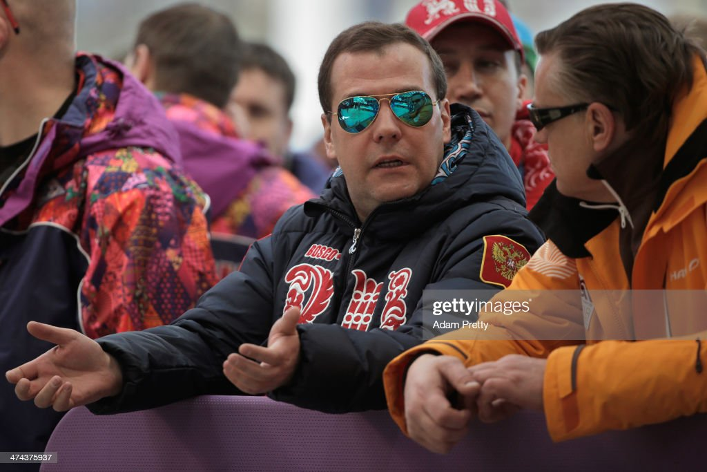 Russian Prime Minister Dmitry Medvedev (L) and Latvia Bobsleigh team coach Zintis Ekmanis speak during the Men's Four-Man Bobsleigh on Day 16 of the Sochi 2014 Winter Olympics at Sliding Center Sanki on February 23, 2014 in Sochi, Russia.