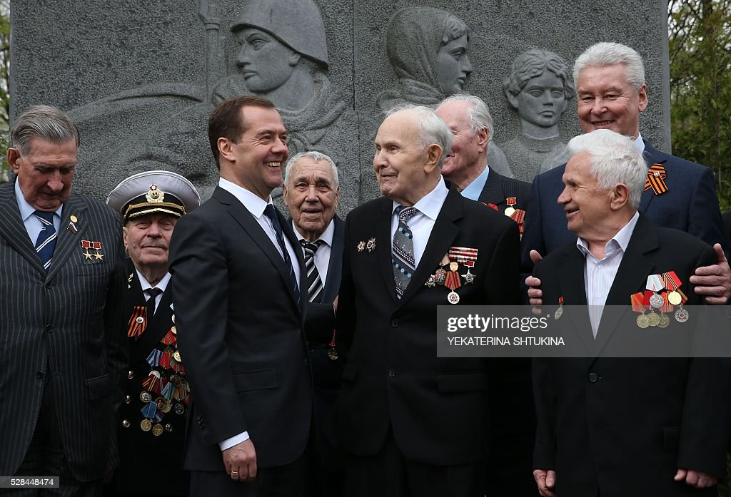 Russian Prime Minister Dmitry Medvedev (3rd L) and Moscow's Mayor Sergei Sobyanin (back R) meet with World War II veterans in Moscow on May 5, 2016. Russia will celebrate the 71st anniversary of the 1945 victory over Nazi Germany on May 9 / AFP / SPUTNIK / Yekaterina Shtukina