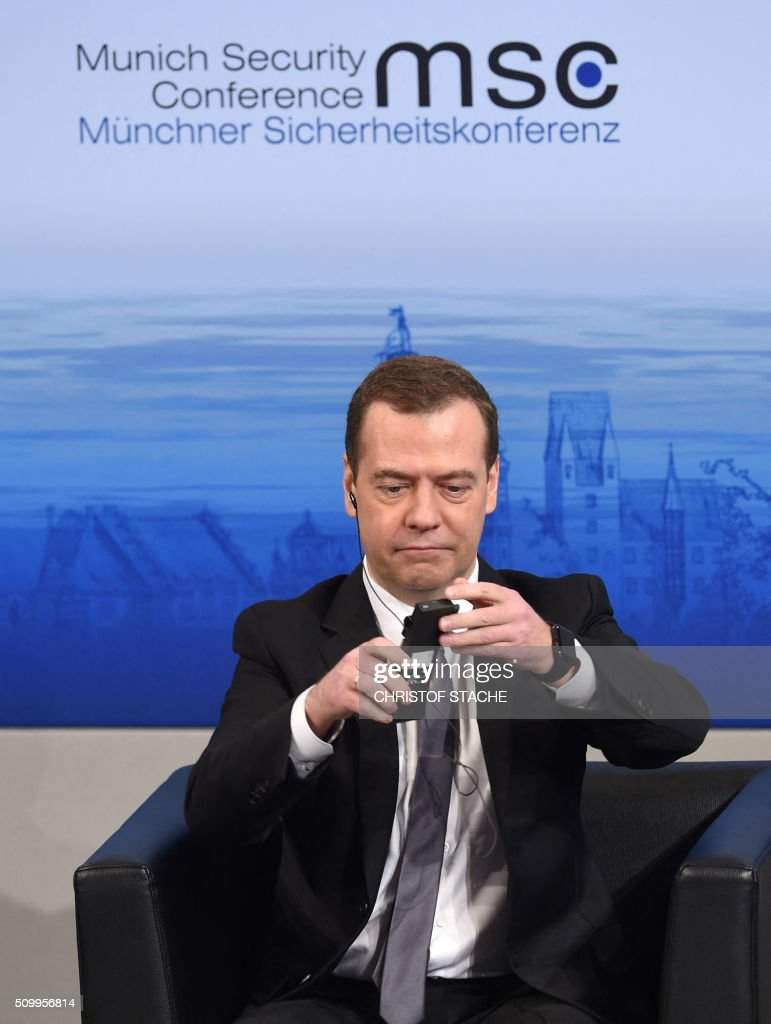 Russian Prime Minister Dmitry Medvedev prepares his headphone during a speech at a panel of the second day of the 52nd Munich Security Conference (MSC) in Munich, southern Germany, on February 13, 2016. / AFP / Christof STACHE