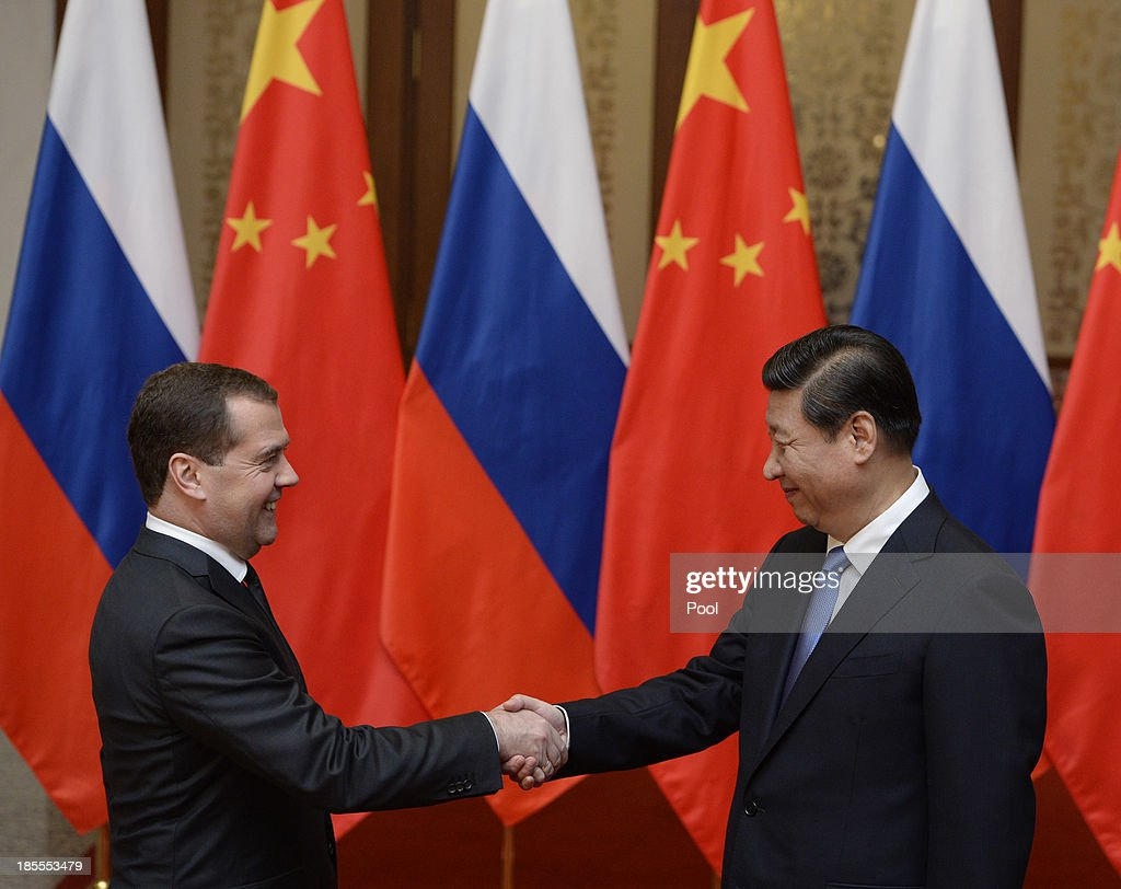 Russian Prime Minister <a gi-track='captionPersonalityLinkClicked' href=/galleries/search?phrase=Dmitry+Medvedev&family=editorial&specificpeople=554704 ng-click='$event.stopPropagation()'>Dmitry Medvedev</a> (L) shakes hands with Chinese President <a gi-track='captionPersonalityLinkClicked' href=/galleries/search?phrase=Xi+Jinping&family=editorial&specificpeople=2598986 ng-click='$event.stopPropagation()'>Xi Jinping</a> (R) before a meeting at the Great Hall of the People on October 22, 2013 in Beijing, China. Medvedev is in China on a two-day visit as a guest of Chinese Premier Li Keqiang to co-chair the 18th regular meeting between the Chinese and Russian heads of government.