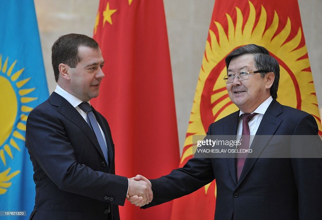 Russian Prime Minister Dmitry Medvedev (L) shakes hands with his Kyrgyz counterpart Zhantoro Satybaldiyev(R) during a welcome ceremony for the Shanghai Cooperation Organization (SCO) summit's participants at the Ala-Archa state residence in Bishkek on December 5, 2012. The top officials of a grouping led by Russia and China met today to discuss regional issues in the Kyrgyzstan's capital.