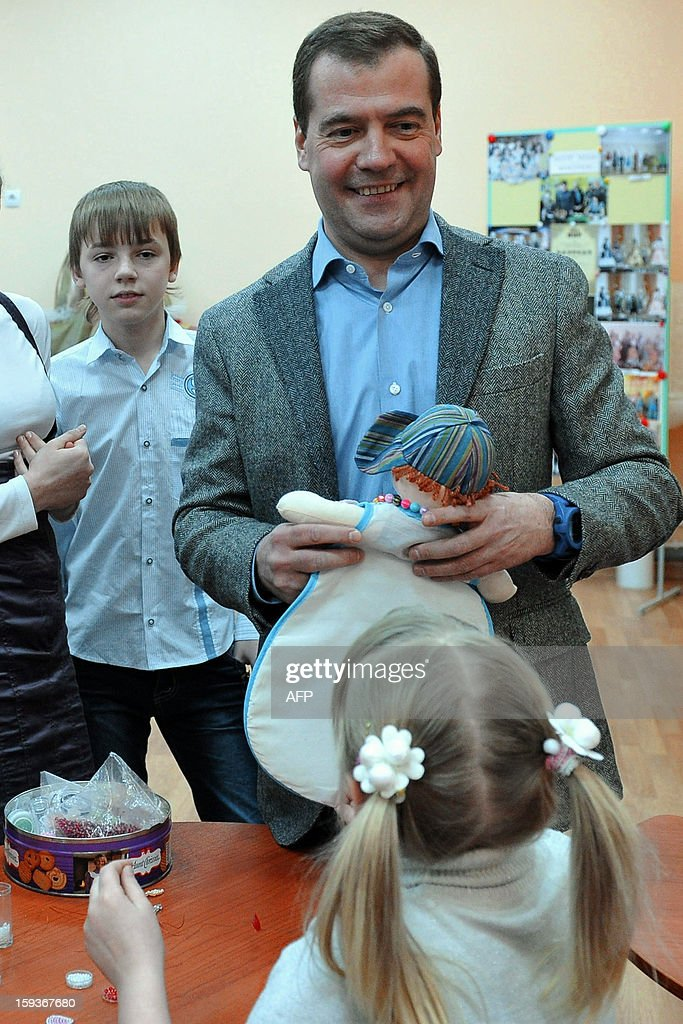 Russian Prime Minister Dmitry Medvedev (C) smiles as he talks with a girl during his visit to the Zvezdny (Star) orphanage in Ivanovo, 300 km from Moscow, on January 11, 2013.
