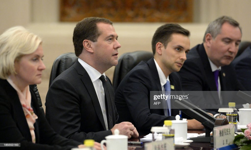 Russian Prime Minister Dmitry Medvedev (2nd L) talks to Chinese President Xi Jinping (unpictured) during a meeting at the Great Hall of the People in Beijing on October 22, 2013.