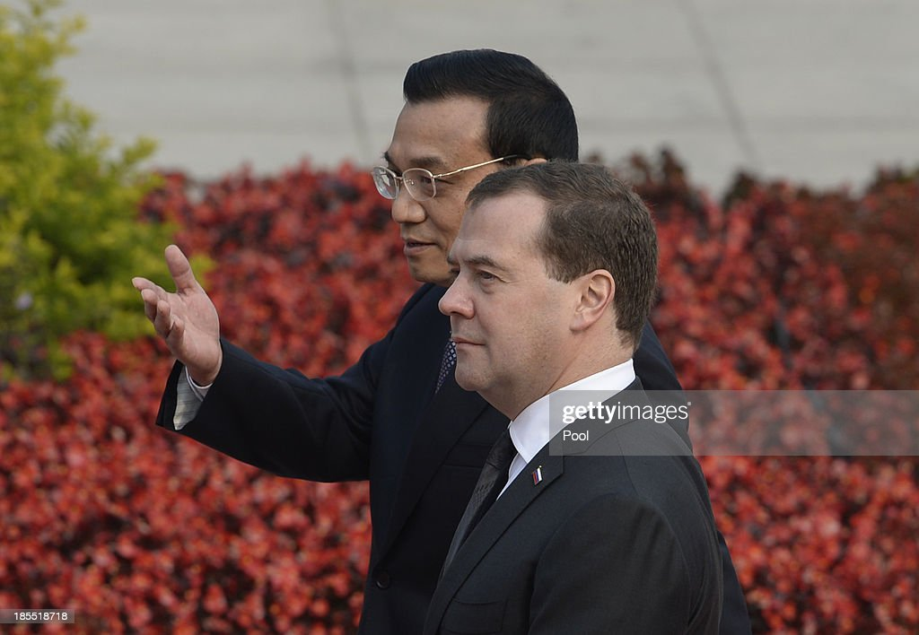 Russian Prime Minister Dmitry Medvedev (R) talks with Chinese Premier Li Keqiang (L) during a welcoming ceremony outside at the Great Hall of the People on October 22, 2013 in Beijing, China. Medvedev is in China on a two-day visit as a guest of Chinese Premier Li Keqiang to co-chair the 18th regular meeting between the Chinese and Russian heads of government.